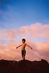 A young boy standing on rocks along a beach in Hawaii