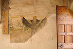 A fresco dating back to the 15th century, under repair in the S. Maria delle Grazie Chiostro, a convent in Gravedona, a town on Lake Como, Italy. A fresco of a saint with his arms outstretched.