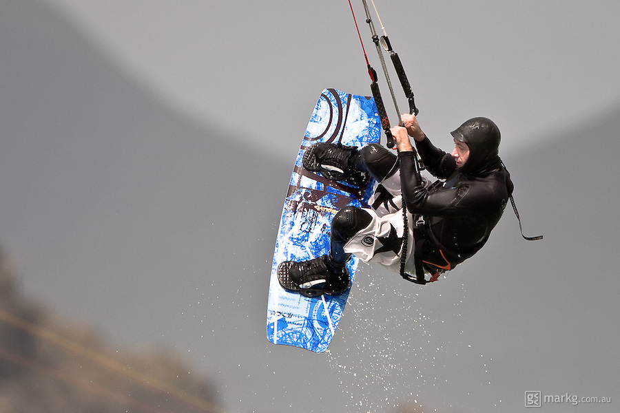 A kiteboarder flies high above the surf at Lyall Bay, Wellington, New Zealand