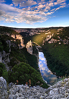 "A view at sunset of the Ardeche river and its gorges, which are actually a wonderful canyon - 35 kms long and 250 meters deep - the river dug for million years in a limestone plateau.  This part of the gorges is placed at about half lenght of the canyon and its main feature is the rock formation visible on the left of the river, know as ""La Cathédrale"" for its vertical, sharp ""spires"". Just to give a sense of scale of this scene, the Cathedral is about 80 meters tall, and I took this picture from a natural balcony at about 200 mts above the river bed. The slice of sky reflected in the river is so sharp and striking, that it almost looks like a rift in the Earth that let one look out to the other side of the planet. This is a stitch of four horizontal frames."