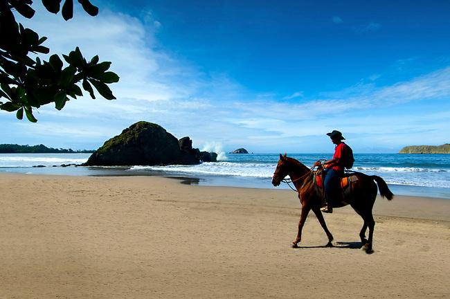 Local Costa Rican cowboy rides horseback over the beaches of Manuel Antonio.