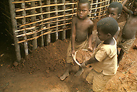 village life in Africa: West Africa, Liberia, Kpelle tribe: children carrying mud, helping in the construction of a wattle-and-daub house.