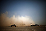 "10/3/2010 Forward Operating Base Dwyer, Helmand Province, Afghanistan.Medevac Helicopters of Charlie Co. 1 Battalion, 214th Aviation Wing, US Army wait for missions on the flightline at Forward Operating Base Dwyer in Helmand Province, Afghanistan...The Helicopter Medevac teams of Task Force Destiny, based at Forward Operating Base Dwyer in Afghanistan's war-torn Helmand Province have a tough job. Servicing a large area that includes still restive southern Marjah, and much of the Helmand River Valley, TF Destiny answers the call to transport gravely wounded US Marines and Afghan civilians from the point of injury in the field to Role 3 trauma centers on bases in the area--often times landing under fire to extract Marines and soldiers that would otherwise succumb to their wounds. After the Medevac helicopter and it's ""chase"" UH-60 Blackhawk companion aircraft get a call, they can be on the ground picking up a patient in as little as 20 minutes--delivering the fallen to a surgical theater within what flight medics refer to as ""the golden hour""--or the hour after a catastrophic injury during which a patients transfer from basic battlefield triage care to a modern trauma surgical unit can mean the difference between life and death. ."