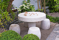 Chess game table and stool seats in backyard patio with buxus boxwood, cornus kousa, in small Oriental Japanese Asian Chinese styled garden design with pebbled walk, outdoor room