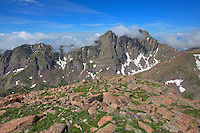 From Humbolt Peak at 14,064 feet, the Crestones - Crestone Needle and Crestone Peak - both rise over 14,000 feet as well. On a beautiful morning, clouds spill over their jagged slopes and into the valley below in this high altitude Colorado landscape.