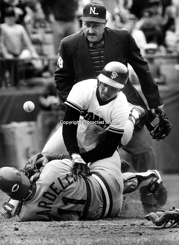 San Francisco Giant Jose Uribe knocks the ball loose from Cincinnati Reds catcher Dan Bilardello, umpire is Dick Sstello(1985 photo by Ron Riesterer)