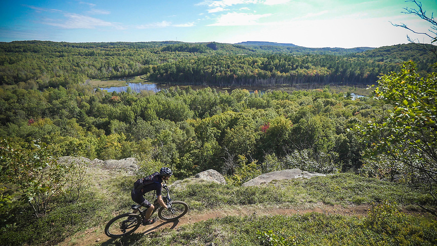 A mountain biker in the Marji Gesick 100 reaches the Panorama Overlook on the RAMBA trail system in Ishpeming, Michigan.
