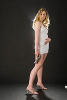 Caucasian blonde woman posing towards camera holding handgun on black seamless