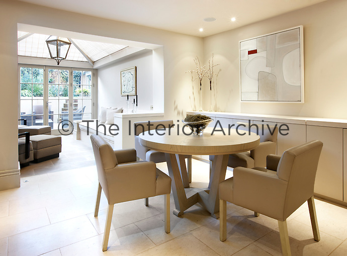 Four leather upholstered chairs surround a small round table in this contemporary dining room that leads into a conservatory sitting area