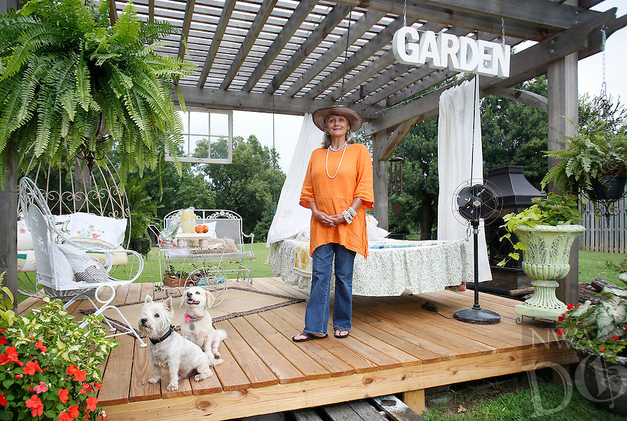 NWA Democrat-Gazette/DAVID GOTTSCHALK  Suzanne Slikard Lentz stands in her favorite personal space with her dogs, the decorated deck in the backyard of her Prairie Grove house Monday, August 10, 2015.