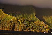 Yacht 'Heron' anchored off the cliffs of Hanavave Bay at sunset, Fatu Hiva,  Marquesas, French Polynesia