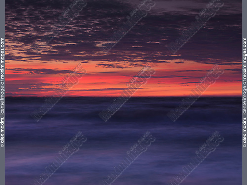 Beautiful dramatic abstract red and blue sunset scenery of lake Huron, Pinery Provincial Park, Grand Bend, Ontario, Canada.