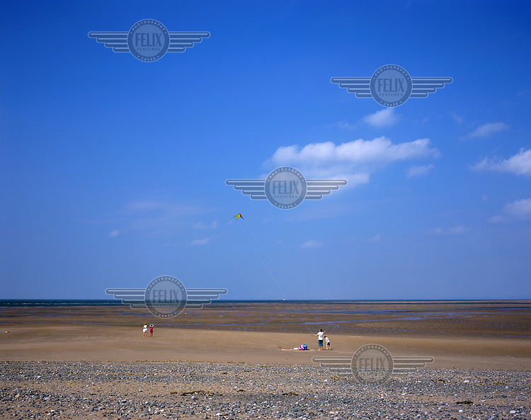 A family fly a kite on a beach in Fleetwood.