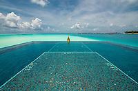 Maldives, Rangali Island. Conrad Hilton Resort. Woman in infinity pool near the ocean. (MR)