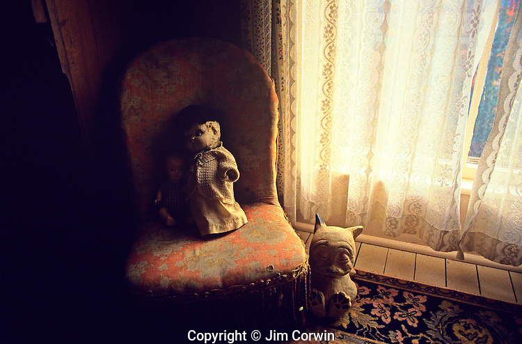 Old dolls in chair with animal doll on floor by window