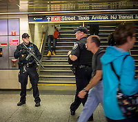 Very visible police officers patrol Pennsylvania Station in New York on Thursday, September 25, 2014 in response to Iraqi Prime Minister Haider al-Abadi's report of an imminent ISIS terrorist plot on the New York and Paris subway systems. Law enforcement and intel agencies are reporting that they know of no plot and the police in New York have been operating at heightened security level already. (© Richard B. Levine)