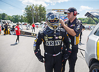 Jun 6, 2016; Epping , NH, USA; NHRA top fuel driver Tony Schumacher is helped with safety gear by a crew member during the New England Nationals at New England Dragway. Mandatory Credit: Mark J. Rebilas-USA TODAY Sports