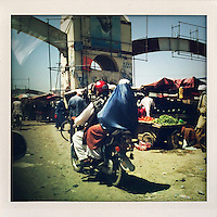 A woman in a burqa rides pillion on a motorbike through a vegetable market.