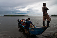 Colombian shellfish pickers embark on a canoe going to the mangrove swamps on the Pacific coast, Colombia, 12 June 2010. Deep in the impenetrable labyrinth of mangrove swamps on the Pacific seashore, hundreds of people struggle everyday, searching and gathering a tiny shellfish called 'piangua'. Wading through sticky mud among the mangrove tree roots, facing the clouds of mosquitos, they pick up mussels hidden deep in mud, no matter of unbearable tropical heat or strong rain. Although the shellfish pickers, mostly Afro-Colombians displaced by the Colombian armed conflict, take a high risk (malaria, poisonous bites,...), their salary is very low and keeps them living in extreme poverty.