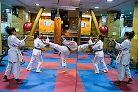 Women practicing Taekwondo at a gym are reflected in a mirroe.