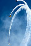 Three airplanes doing a loop with white smoke trails over blue sky. Aerobatics at Canadian International Air Show in Toronto.