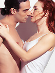 Closeup portrait of a sexy couple kissing. Young man with bare torso and a red-haired woman.
