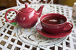 A small bright pink teapot and a bright pink cup and saucer sit on a white wrought iron table in a tea room. There is coffee in the cup.