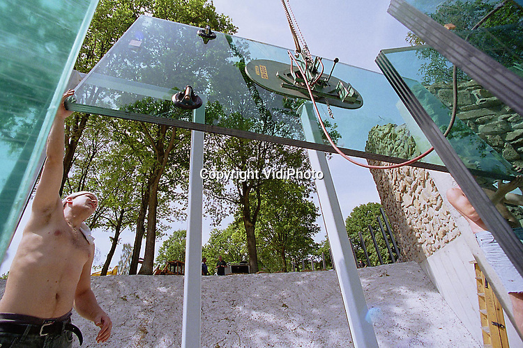 Foto: VidiPhoto..RHENEN - In Ouwehands Dierenpark in Rhenen zijn maandag de centimeters dikke ramen geplaatst voor het ijsberenbassin. Het dierenpark bouwt een .splinternieuw onderkomen van 3 miljoen gulden voor de ijsberen. Bijzonder is het glazen bassin, waarin bezoekers op ooghoogte de ijsberen voorbij kunnen .zien zwemmen. Half juni moet alles klaar zijn.