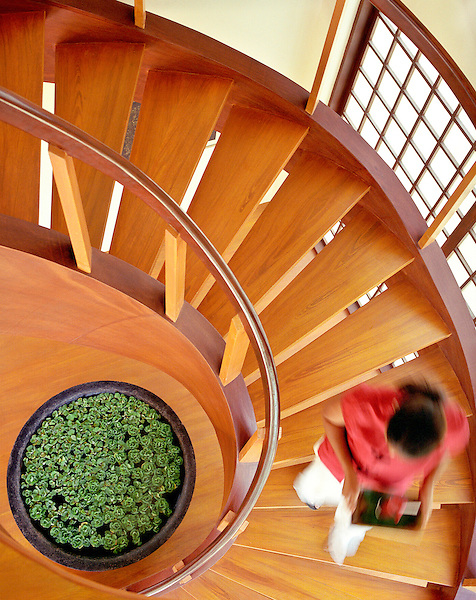 BORACAY ISLAND, PHILIPPINES : A waitress carries a drink down a spiral staircase inside Prana Restaurant at Mandala Spa. Boracay Island, Philippines, South East Asia.