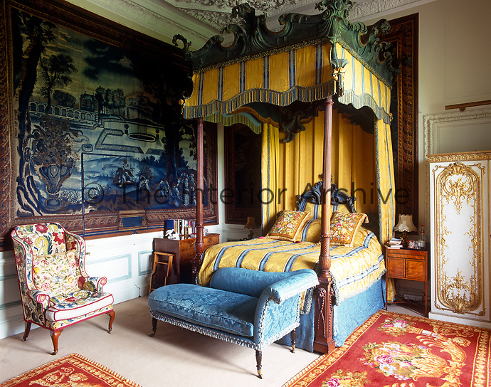 An antique four-poster bed with yellow and blue striped bed hangings dominates a bedroom decorated with a blue tapestry