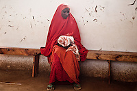 Mariam Mohamud, 30, has given birth to a baby girl during the night. Mariam wraps her child in a red cloth and holds her at a health screening center run by Doctors Without Borders in Dagahaley  refugee camp in Kenya.