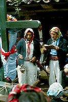 Guatemala, Ixil Maya Indian men praying while procession stopped at a cofradia (religious brotherhood) in Nebaj (Dept. El Quiche)