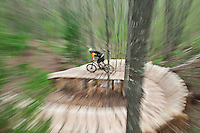 Mountain biker Jeremy Pletka rides the Woopidy Woo single track trail over wooden bridges along Brockway Mountain in Copper Harbor Michigan.