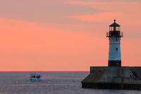 A charter fishing boat heads out to Lake Superior at sunrise.