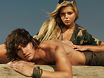 Young beautiful woman in army style outfit and a young man on the beach