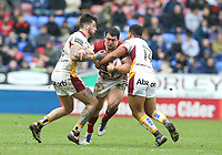Wigan Warriors' Ben Flower is tackled by Huddersfield Giants' Oliver Roberts (left) and Kruise Leeming (right) <br /> <br /> Photographer Stephen White/CameraSport<br /> <br /> Betfred Super League Round 5 - Wigan Warriors v Huddersfield Giants - Sunday 19th March 2017 - DW Stadium - Wigan<br /> <br /> World Copyright &copy; 2017 CameraSport. All rights reserved. 43 Linden Ave. Countesthorpe. Leicester. England. LE8 5PG - Tel: +44 (0) 116 277 4147 - admin@camerasport.com - www.camerasport.com