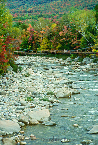 Clear New England river with suspension walking bridge in fall