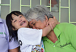 Maria Hilvano gets a hug from 9-year old Gabriel Ong, a girl with Down Syndrome, in Manila, the capital of the Philippines. Both are members of Kaisaka, a mothers' group that assists families which have members with disabilities.