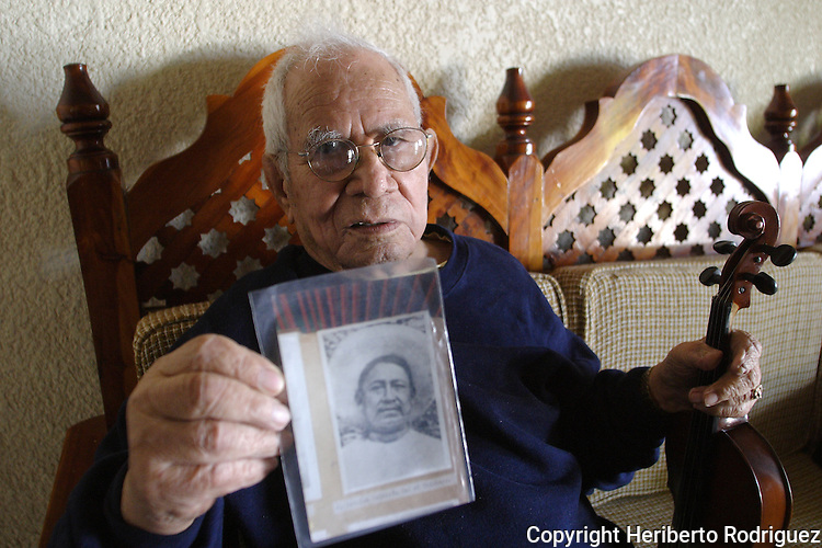 Mexican folk fiddler Juan Reynoso holds a portrait of his violin teacher don Isaias Salmeron in his house in the town of Vivente Riva Palacio, in southern Michoacan state, December 222, 2003. Juan Reynoso is known as the Paganini of the Hotlands, he was born in 1912 at Coyuca de Catalan in Guerrero state and he died at age 94. Photo by Heriberto Rodriguez..