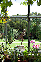 A view from the conservatory towards a running statue in the grounds of the castle
