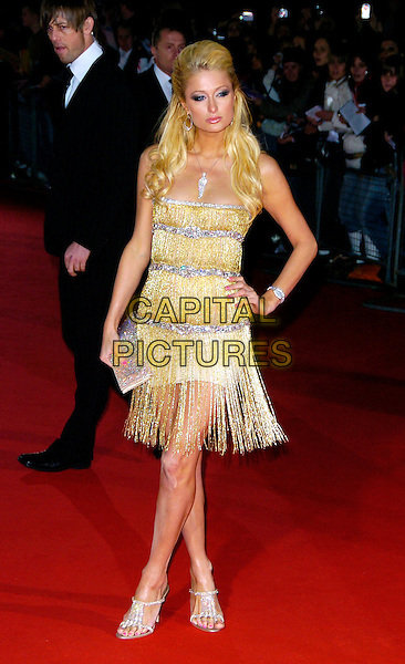 PARIS HILTON.Arrivals at World Music Awards 2006, Earls Court, London, UK..November 15th, 2006.full length gold silver dress tassles clutch purse hand on hip shoes.CAP/CAN.©Can Nguyen/Capital Pictures