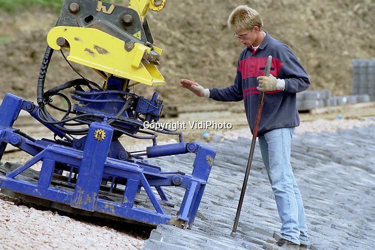 Foto: VidiPhoto..DODEWAARD - Werknemers van een aannemersbedrijf leggen op dit moment de stenen voor de beschoeiing aan de buitenzijde van de Waaldijk bij Dodewaard. De werkzaamheden zijn onderdeel van het Deltaplan Grote Rivieren, dat eind 2000 afgerond moet zijn. De stenen beschoeiing bij Dodewaard is nodig omdat de dijk daar in de bocht van de rivier De Waal ligt en bij hoog water dan extra wordt belast..