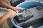 A craftsman works on an ink stone made from local slate at a temporary workshop in Ogatsu, Ishinomaki City, Japan on 9 Sept. 2012.  Photographer: Rob Gilhooly