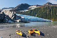 Kayaks along a beach at the tidewater face of Harriman glacier, Chugach mountains, Chugach National Forest, Prince William Sound, southcentral, Alaska.