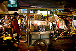 A vendor pushes her cart though the busy street in Phnom Penh, Cambodia.