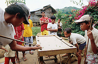Philippines. Negros Island. Province of Negros Occidental, located in the  Western Visayas region. Barangay (village) Camao. Boys and young men play pool. Billiard balls. Wood table. © 1999 Didier Ruef