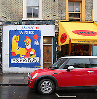 """Austin Mini parked in front of a """"Spice"""" coffee shop and a colorful spray paint graffiti building showing a figure of the Front Populaire (Popular Front) in Miro's style and """"Aidez Espana"""" written, Notting Hill, London, UK. Picture by Manuel Cohen"""