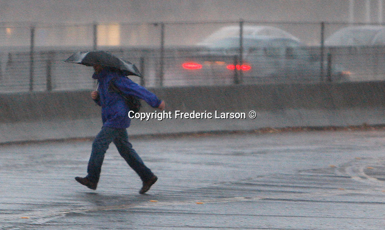 A pedestrian runs across Redwood Highway in Mill Valley, California as heavy rains slammed in the Bay Area forcing motorist to take it slow.