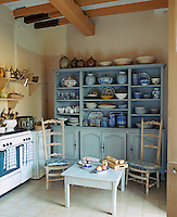 A pair of high-backed kitchen chairs in front of the large blue dresser in the kitchen displaying a collection of ceramics from North Africa, Andalucia, China and Holland