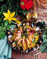 Prepared dish of Spanish Paella consisting of rice, green peas, asparagus, steamed clams, lobster, shrimp and seasoned with saffron.